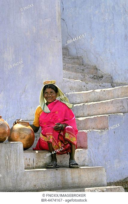 Native woman with water jugs, water bearer sitting on steps, Amber Fort, Jaipur, Rajasthan, India