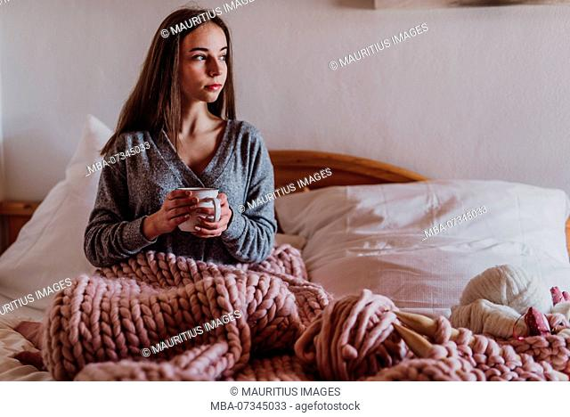 young woman sitting in bed with a cup of tea