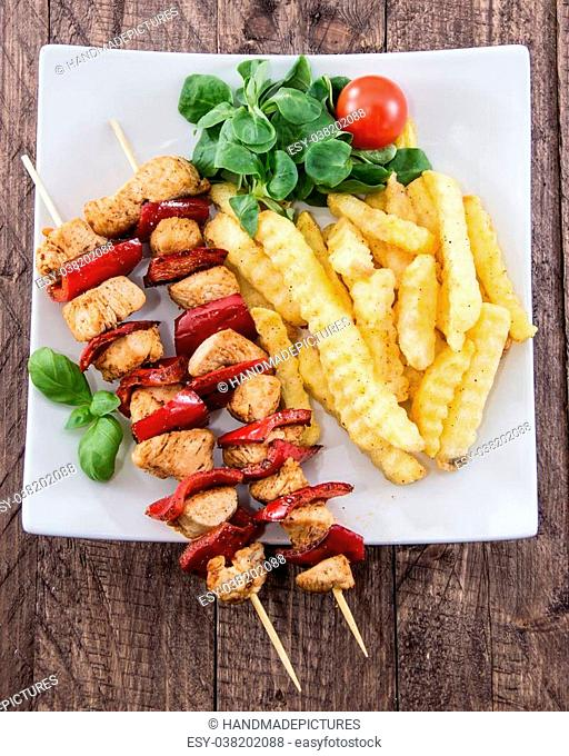 Fresh Skewer with french fries on wooden background