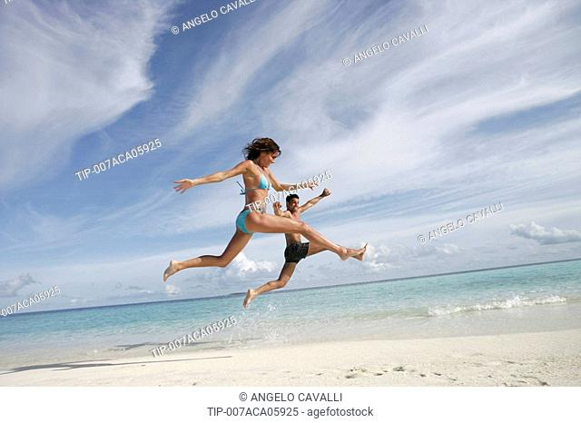 Couple jumping outdoors