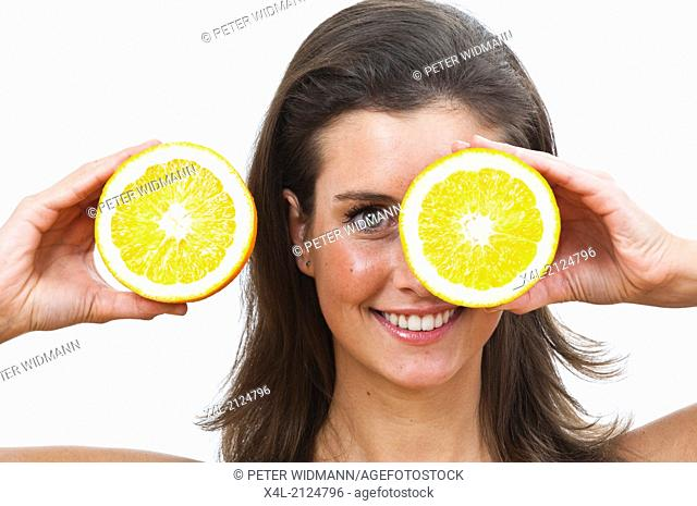Young woman holding two half oranges in front of her eyes (model-released)