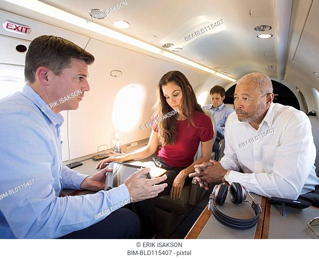 Business people talking on airplane
