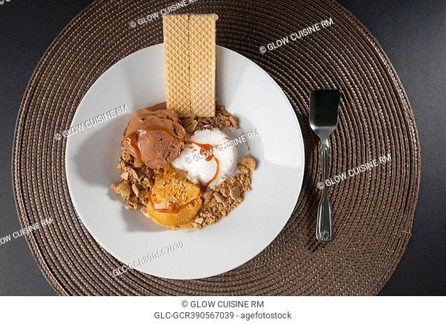Assorted ice creams scoops garnished with nuts and wafers
