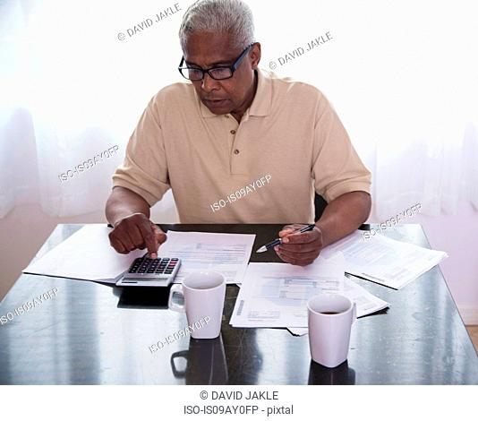 Senior man sitting at table, surrounded by paperwork, using calculator