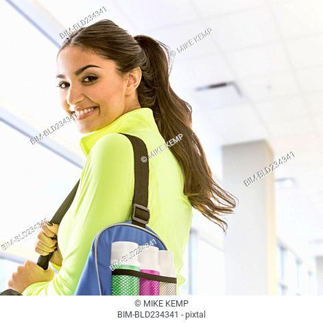 Smiling Mixed Race woman carrying bag at gymnasium