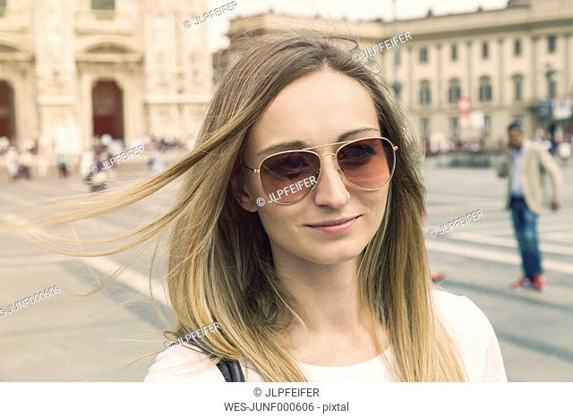 Italy, Milan, portrait of smiling blond tourist with sunglasses in front of Milan Cathedral