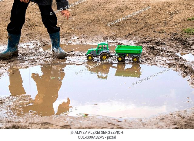 Legs of male toddler wearing rubber boots playing with toy tractor in muddy puddle