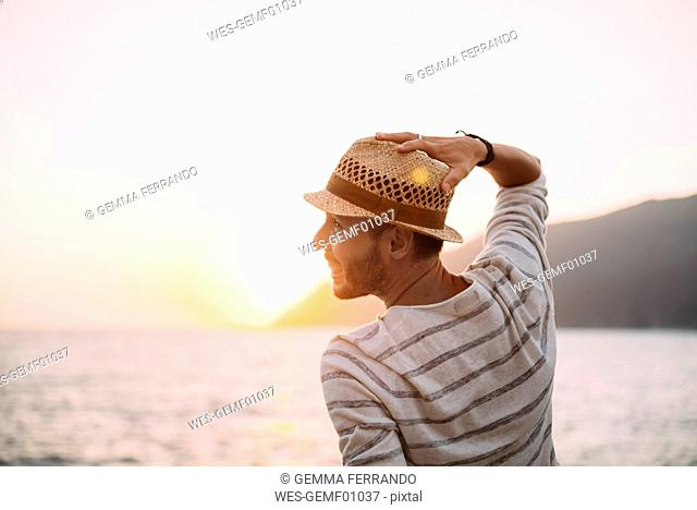 Greece, Cylcades Islands, Amorgos, man enjoying the sunset next to the sea