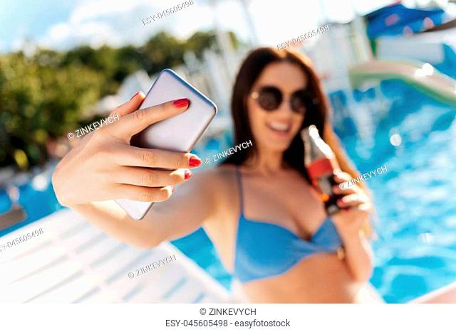 Summer pic. The focus being on a dainty hand of a charming young woman taking a selfie of herself and a bottle of fizzy drink with a swimming pool in the...