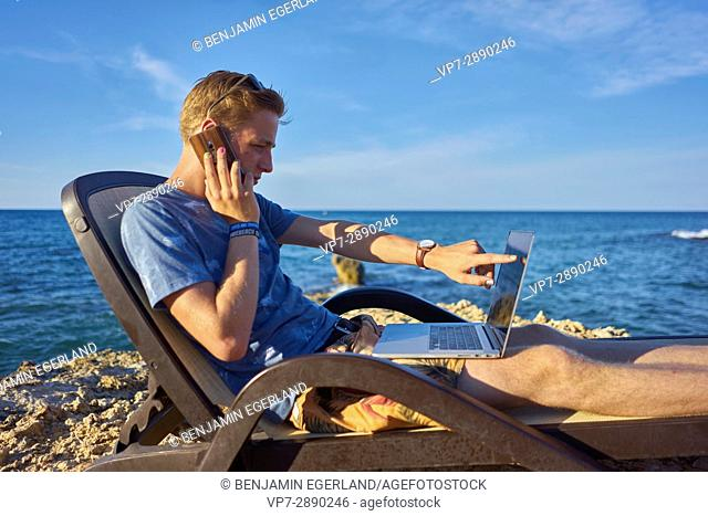 young man using mobile phone and laptop computer in sunbed next to sea in holiday location Hersonissos, Crete, Greece