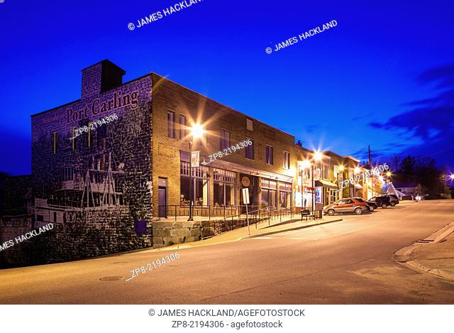 A strip of commercial buildings erected in 1932 with the 'Welcome to Port carling' mural at dusk in downtown Port Carling, Ontario , Canada