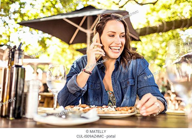 Woman at sidewalk cafe making telephone call