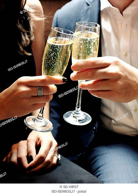 Young couple toasting with champagne glasses, mid section