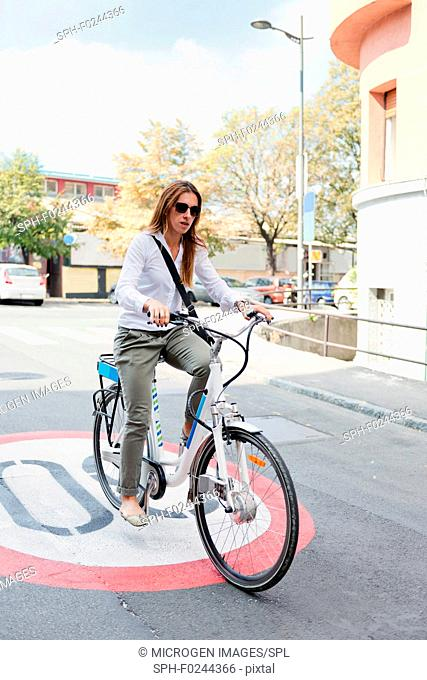Young business woman on electric bicycle