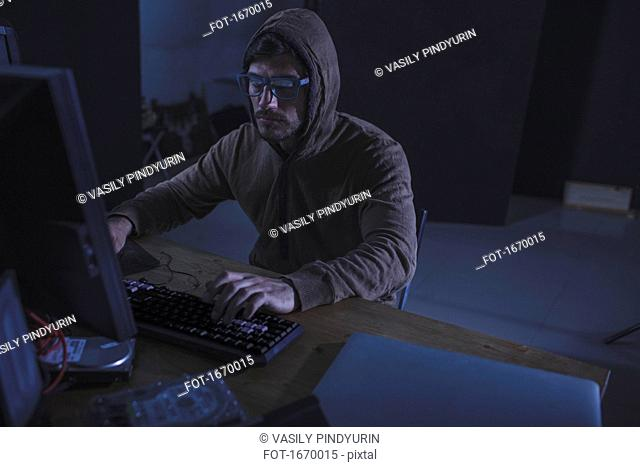 Serious computer hacker wearing hooded shirt using desktop computer at table in abandoned room