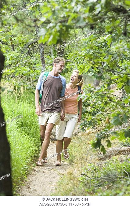 Mature couple walking in a forest and looking at each other