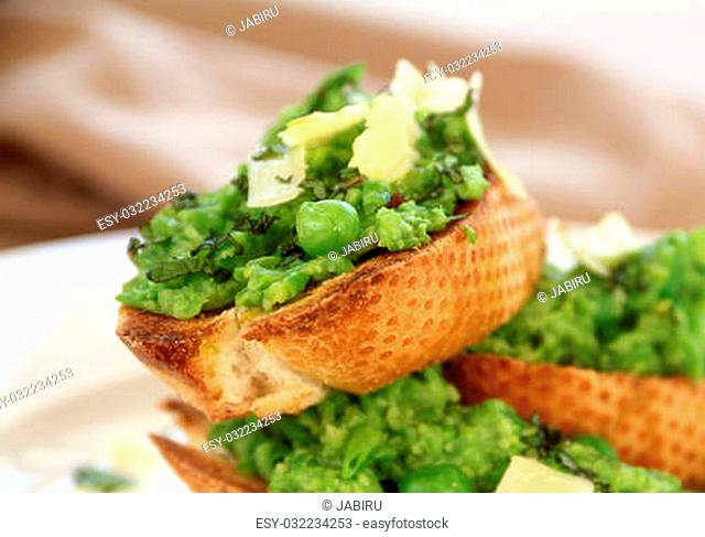 Delicious green pea baguettes with shaved cheese and mint with avocado oil