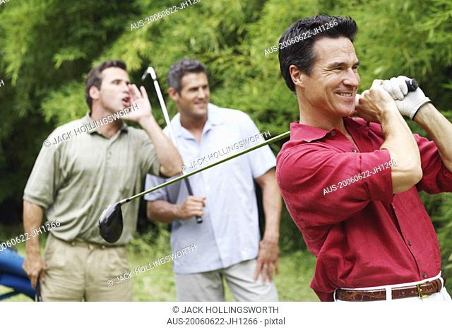Mature man swinging a golf club with his friends standing behind him