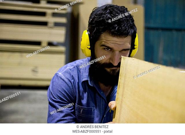 Craftsman with hearing protection examining a wooden plank