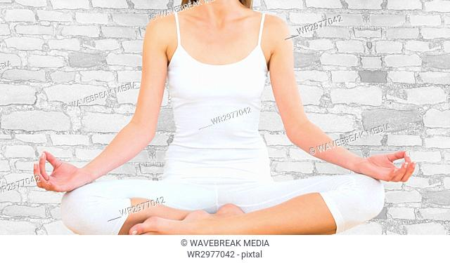 Woman mid section meditating against white brick wall