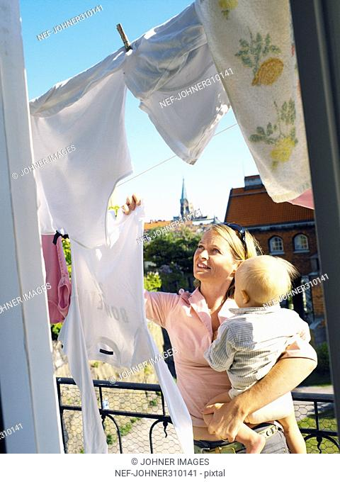 A mother with her child hanging laundray