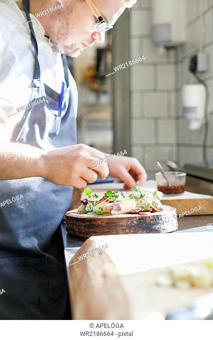 Chef preparing dish at counter in kitchen