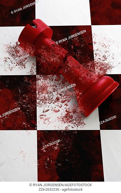Close-up of a cracked and shattered three-dimensional red castle on black and white chess board. When empires fall