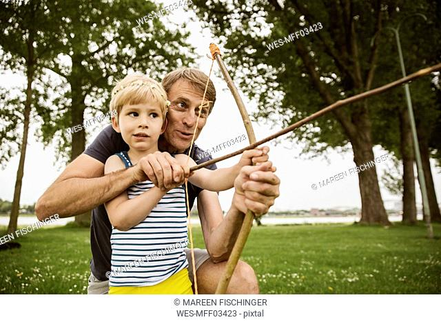 Father and son playing with self made bow and arrow