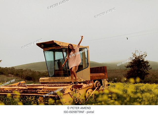 Young woman in field of yellow wildflowers standing on top of abandoned combine harvester, portrait, Jalama, California, USA
