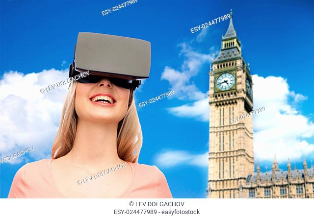 technology, virtual reality, entertainment, travel and people concept - happy young woman with virtual reality headset or 3d glasses over big ben tower and sky...