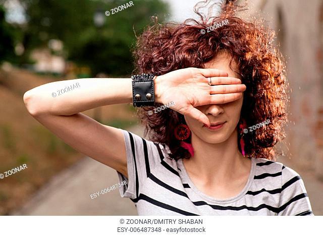 Women hiding her eyes by open palm