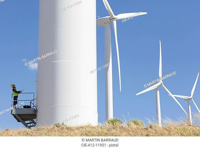 Worker examining wind turbine in rural landscape