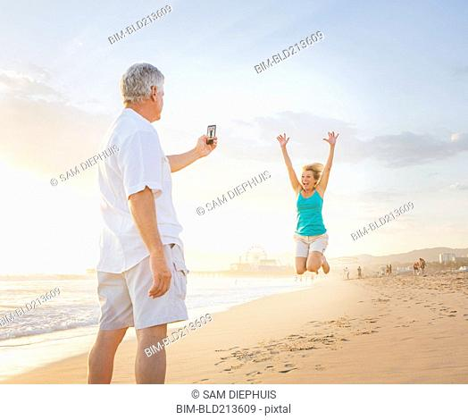 Caucasian man taking cell phone photograph of wife on beach