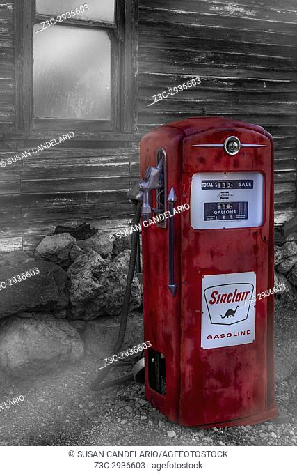 Sinclair Gas Pump SC - Red vintage Sinclair Gasoline Pump still stands by an old wooden structure with the setting sun reflected in the window