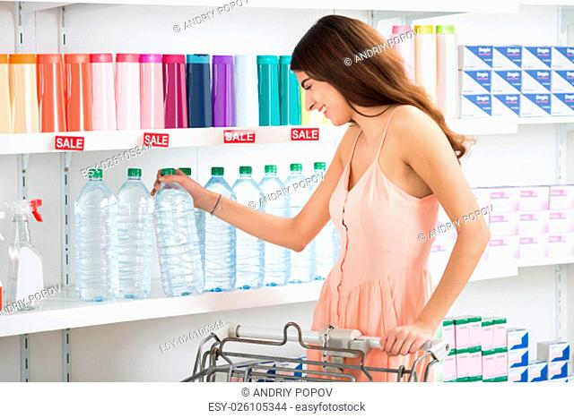 Happy young woman buying bottle of mineral water in supermarket