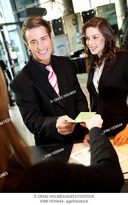 A business man and woman checking into a hotel in Birmingham, West Midlands