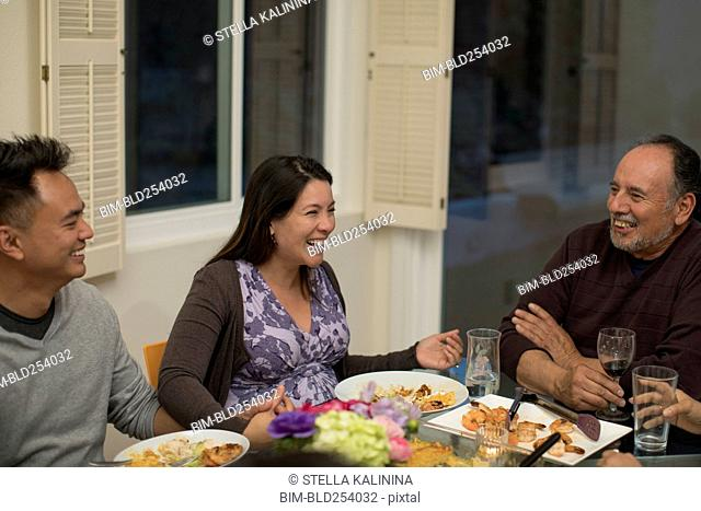 People laughing at dinner table