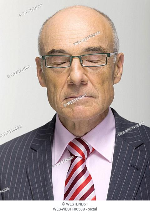 Portrait of a Senior businessman eyes closed, close-up