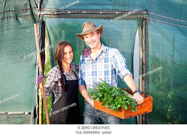 Young woman and man with vegetables grown on farm