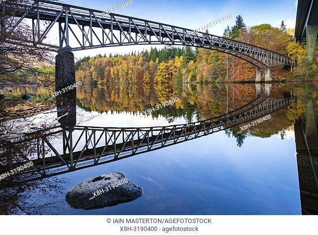 Spectacular late autumn tree colours and bridge is reflected in the waters of Loch Faskally in Pitlochry, Perthshire, Scotland, UK
