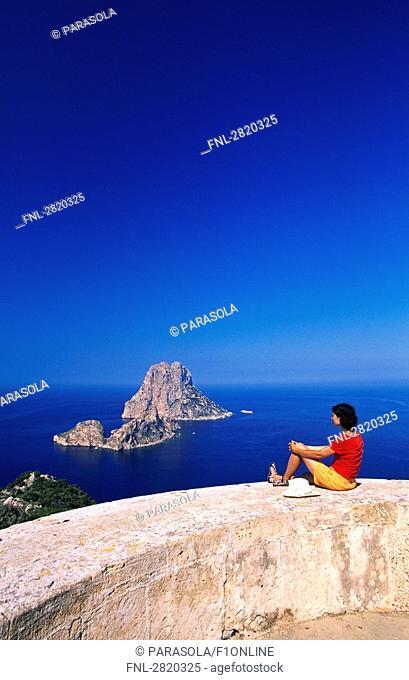 Woman sitting on tower, Es Vedra, Ibiza, Balearic Islands, Spain