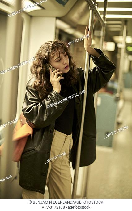 Woman in public transport, using smartphone, Berlin, Germany