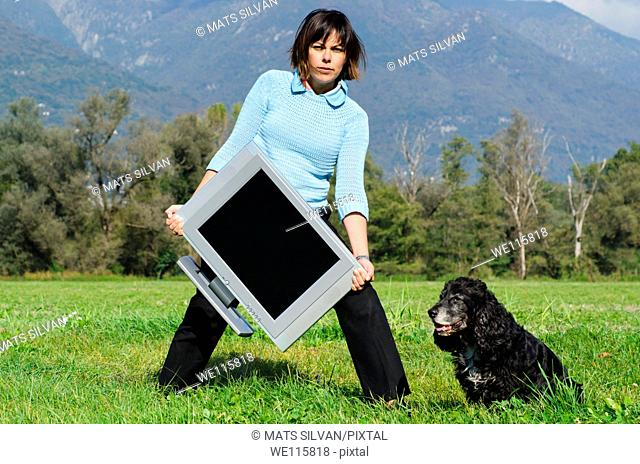 Elegant woman standing up on the field and holding a television and she have a dog