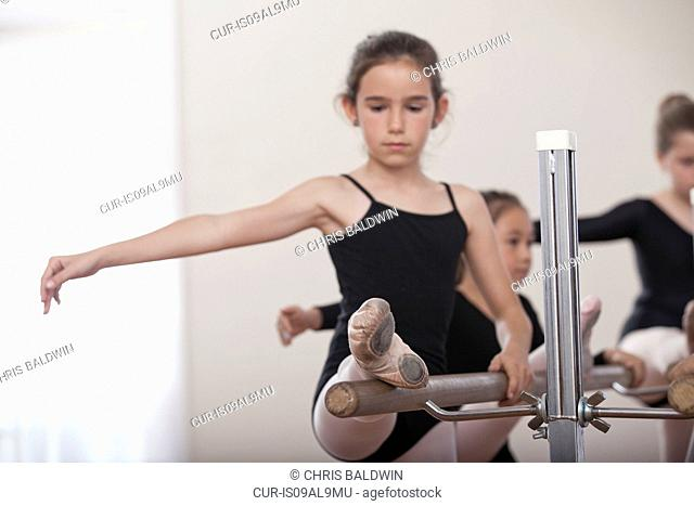 Young ballerina practicing at barre in ballet school