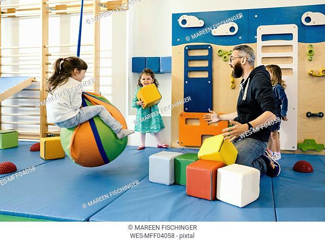 Pre-school teacher and happy children playing in gym room in kindergarten