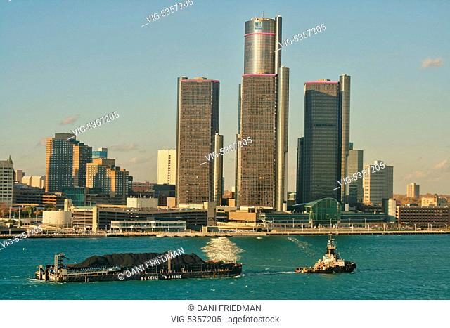 A tugboat pulls a barge loaded with petroleum coke (petcoke) along the Detroit River with the skyline of the city of Detroit, Michigan, USA in the background