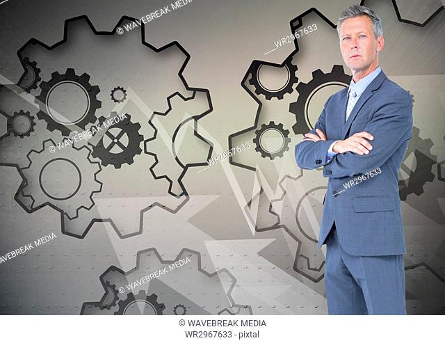 Digital composite image of businessman with arms crossed standing against gears