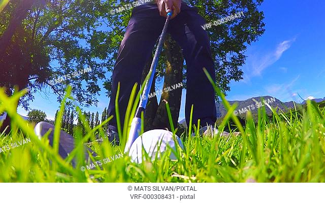 Golfer Making a Golf Swing and Hitting the Golf Ball on the Grass in Ticino, Switzerland