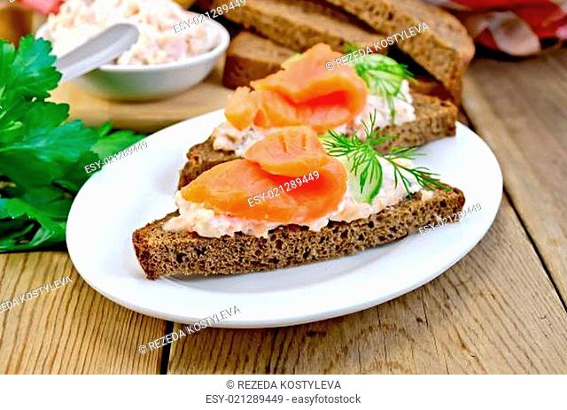 Sandwiches on two pieces of rye bread with cream, dill, cucumber and salmon in a white plate on a wooden boards background