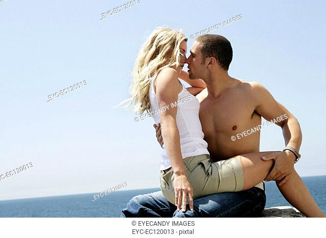 Woman straddling bare-chested man on rock above the sea